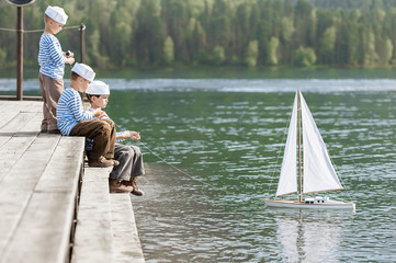 Boys sailors with model yachts on the quay of the mountain lake