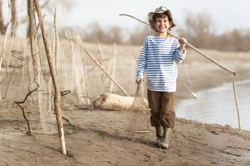 Boy fishing on the bank of the river