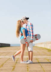 couple with skateboard kissing outdoors
