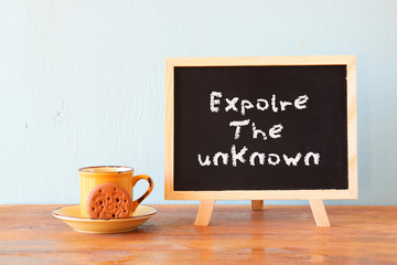 blackboard with the phrase explore the unknown next to cup of co
