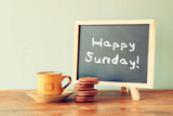 blackboard with the phrase happy sunday written on it and cup of
