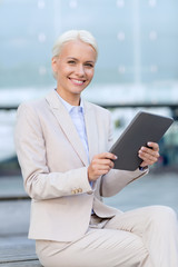 smiling businesswoman with tablet pc outdoors