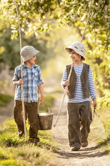 Boys go fishing with fishing rods on a rural street