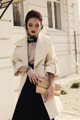 beautiful woman in elegant beige coat and silk scarf