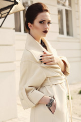 beautiful elegant lady with dark hair in luxurious beige coat