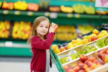 Little girl choosing an apple in a store