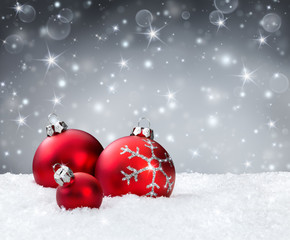 red baubles on snow with silver sparkle background