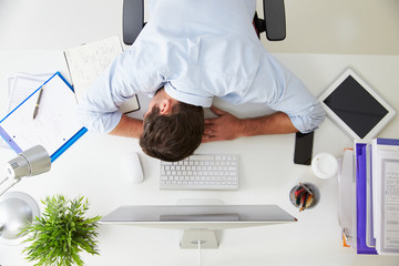 Overhead View Of Tired Businessman Resting By Computer