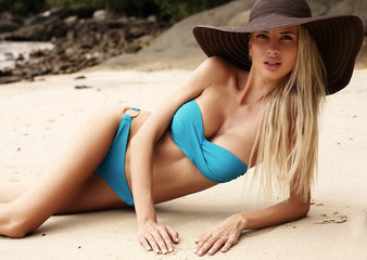 girl with blond hair in bikini and elegant hat relaxing on beach