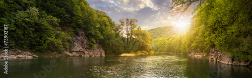 Aluminium Rivier forest river with stones on shores at sunset