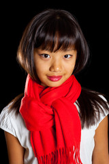Beautiful smiling Asian girl in a red scarf