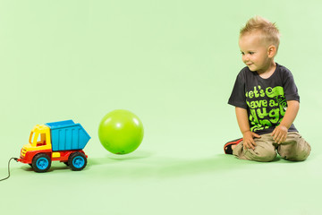 Blond boy playing with colorful car toy green background