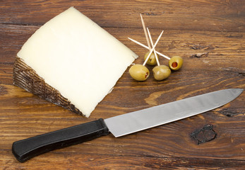 cheese on a wooden rustic table with olives