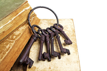 Vintage books and old keys on a white background