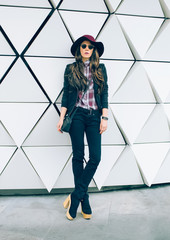 girl in a stylish hat on a city street. fashion style