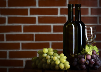 Wite and red wine bottles on brick wall background