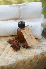 A bottle of star anise essential oil on the woven surface