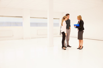Estate Agent Showing Empty Office Space To Potential Clients