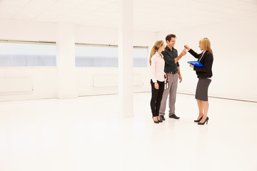 Estate Agent Handing Over Keys To Office Space