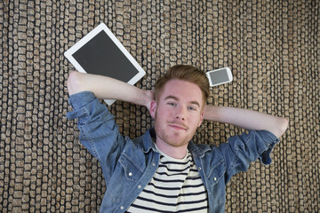Above view of a man lying on floor with tablet PC.