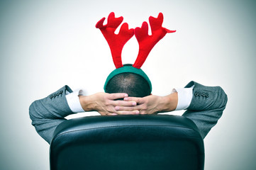 man with a reindeer antlers headband in his office chair