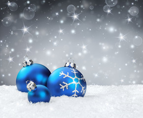 blue baubles on snow with silver sparkle background