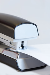 Closeup of a grey office stapler stapling white paper