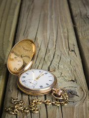 gold pocket watch and chain against  aged wood