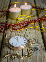 gold pocket watch and chain with decorations and candles against