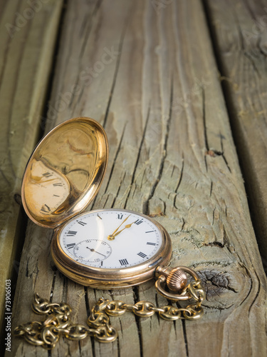 gold pocket watch and chain against  aged wood - 73906503