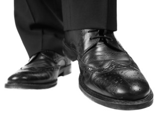 Person in black suit and shoes lifting one foot towards white
