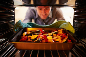 Man Putting Dish Of Vegetables Into Oven To Roast