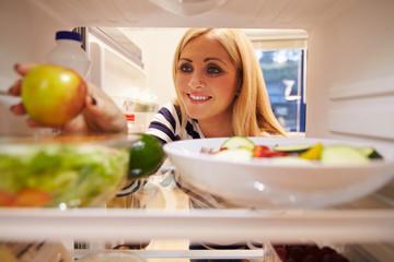 Woman Looking Inside Fridge Full Of Food And Choosing Apple