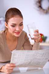 Happy young woman having healthy breakfast in kitchen