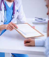 Doctor male giving patient folder with  paper in her office,
