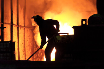 Man is working in the splashing molten iron - Stock Image