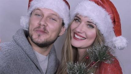 Young happy couple wearing santa's hats singing carols.