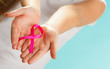 pink breast cancer awareness ribbon on womans hands - 73915545