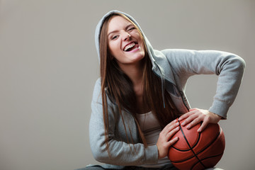 Funny sporty girl holding basketball winking
