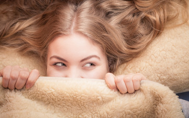 woman lying in bed under blanket