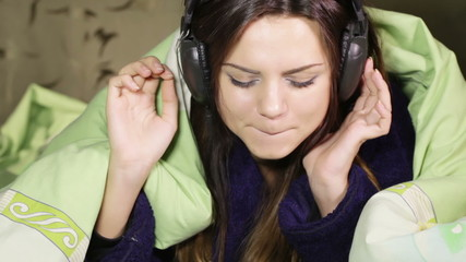 Girl with headphones in bed home