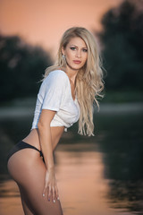Portrait of young sexy blonde girl in bikini posing