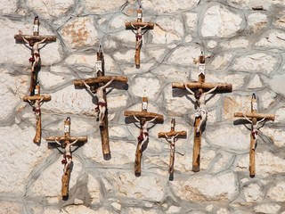 Many wooden crosses on the wall background.