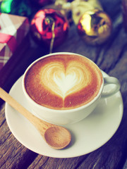 Coffee latte art and the X-mas present box on the wood backgroun