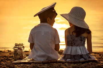 Boy and girl sitting on the shore of the lake at sunset