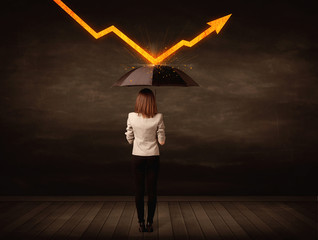 Businesswoman standing with umbrella keeping orange arrow