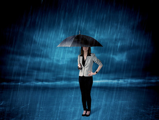 Business woman standing in rain with an umbrella