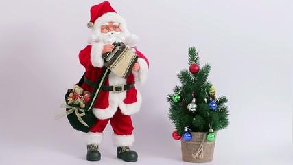 Santa playing the accordion near a Christmas tree