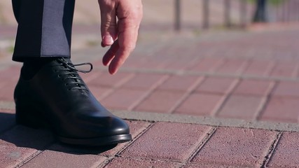 man tying  shoelaces on leather shoes