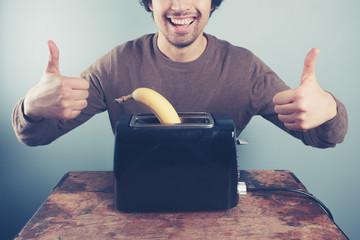 Young man toasting banana giving thumbs up